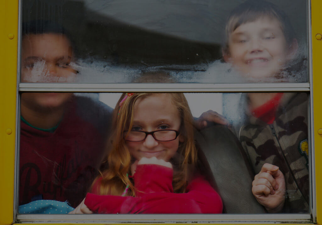 Kids looking out the window of a bus